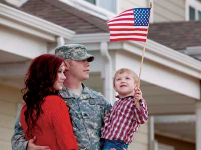 Military family with toddler holding flag