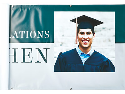 Graduate in cap and gown on banner