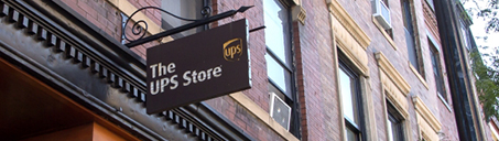 Sign hanging outside a brownstone building with The UPS Store logo
