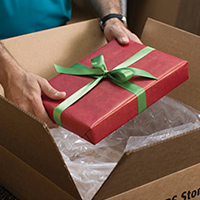 Man placing wrapped gift into a shipping box
