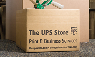 A toy train packaged inside of a The UPS Store box on a red background next to the letter ING