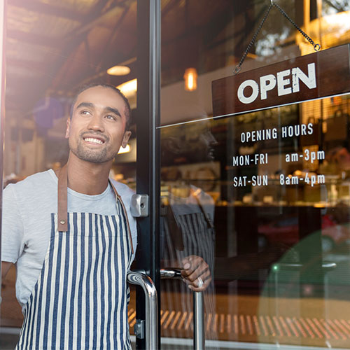owner smiling opening doors to business