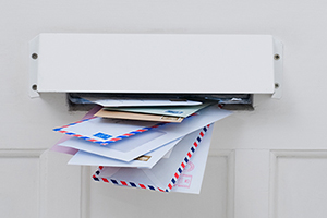 Mail slot in door filled with mail